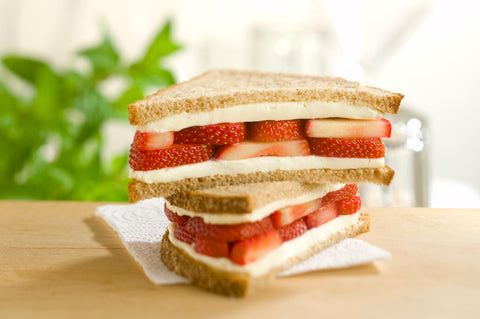 a cream cheese and strawberry sandwich on very thin bread