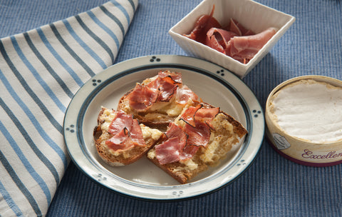 A prosciutto and brie tartan on a plate with a napkin