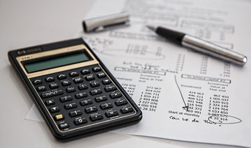 small calculator and pen sitting on top of a budget statement