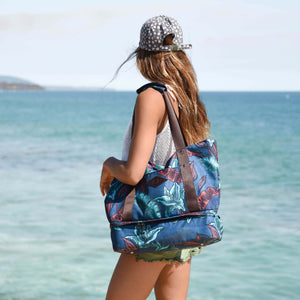 woman wearing a grey hat carrying the salt atlas drifter tote bag in blue lily print with a view on the ocean