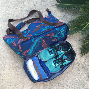 pair of blue running shoes and two towels in the bottom shoe compartment of the salt atlas drifter tote bag in blue lily print