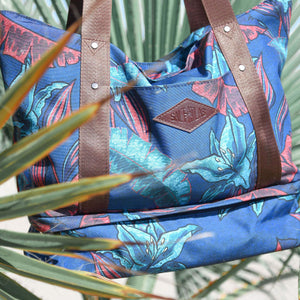 salt atlas drifter tote bag in blue lily print suspended in between tropical plants