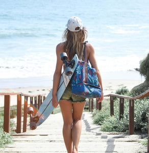 woman wearing a white hat, carrying a skateboard and the salt atlas drifter tote bag in blue lily print on her way to the beach