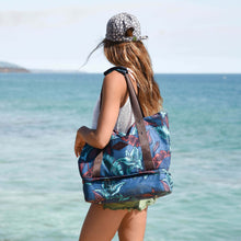 Load image into Gallery viewer, woman wearing a grey hat carrying the salt atlas drifter tote bag in blue lily print with a view on the ocean