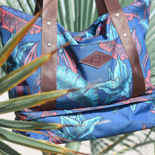 Load image into Gallery viewer, salt atlas drifter tote bag in blue lily print suspended in between tropical plants