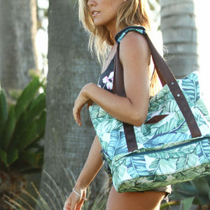 woman carrying the salt atlas drifter tote bag in island green print, in front of a palm tree