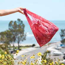 Load image into Gallery viewer, woman holding the salt atlas foldable eco bag in the aloha coral print