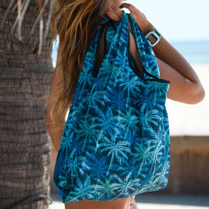 woman carrying the salt atals foldable eco bag in blue palms print on her shoulders at the beach