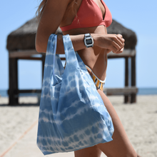 Load image into Gallery viewer, woman in swimwear holding the salt atlas foldable eco bag in tie dye print at the beach