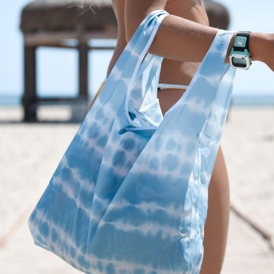 woman in swimwear holding the salt atlas foldable eco bag in tie dye print at the beach
