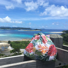 Load image into Gallery viewer, salt atlas foldable eco bag in tropical white print with a ocean background