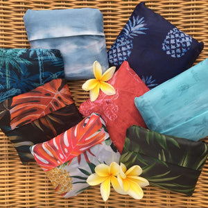 eight salt atlas foldable eco bags in eight different prints: tropical white, tropical black, tropical green, indigo pineapple, surfy, tie dye, aloha coral, and blue palms