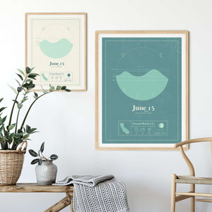 two wooden framed picture of the personalized tide poster by salt atlas in the mint & créme and Tahiti teal colors in a home setting. These are custom posters showing the tide, weather, and moon phase for a special day, like an anniversary or birthday.