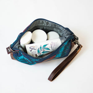 various cosmetics and sunscreen inside the salt atlas rover crossbody bag in blue lily print