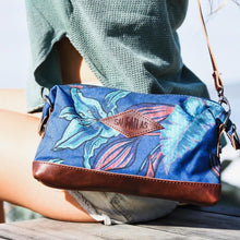 Load image into Gallery viewer, seated  woman with the salt atlas rover crossbody bag in blue lily print