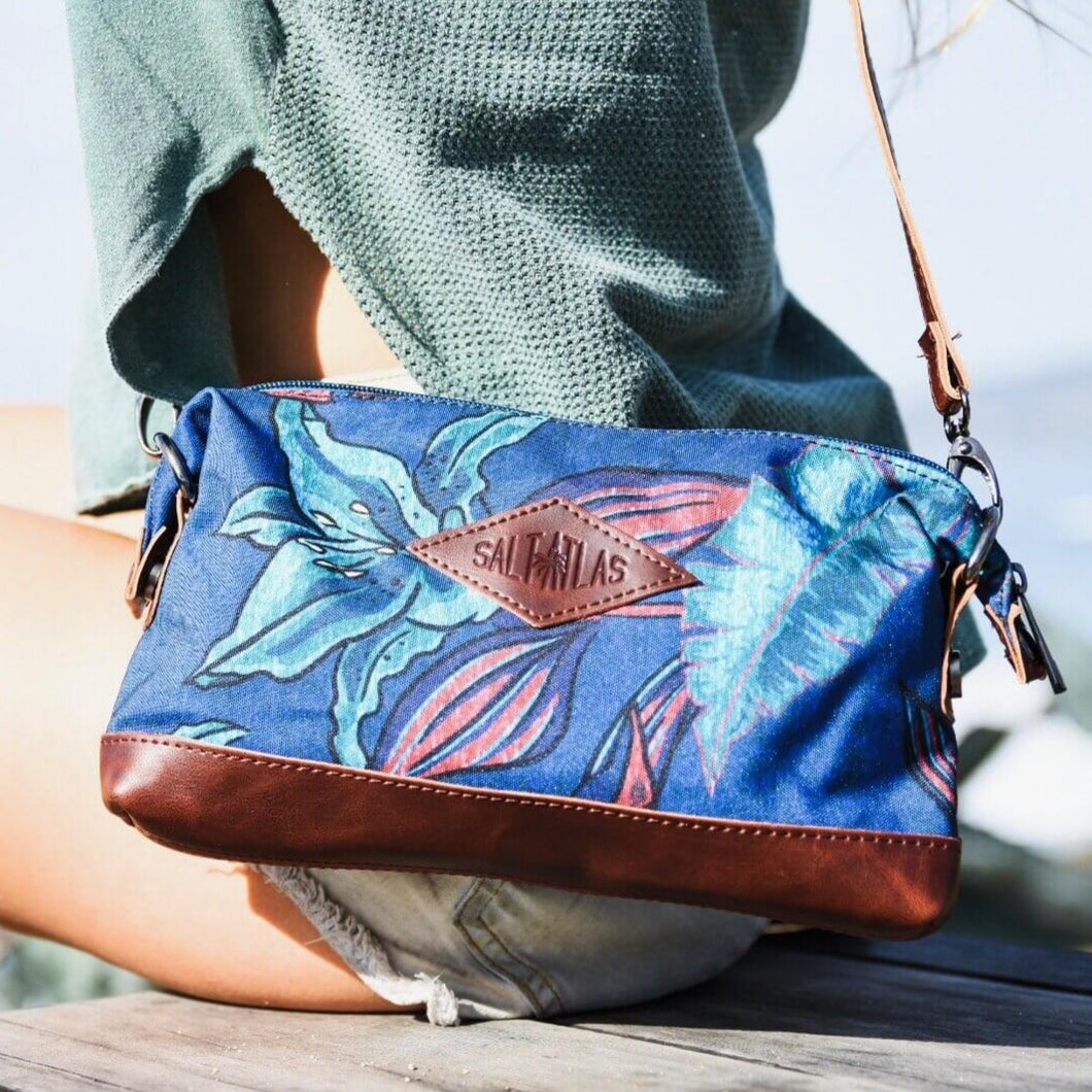 seated  woman with the salt atlas rover crossbody bag in blue lily print