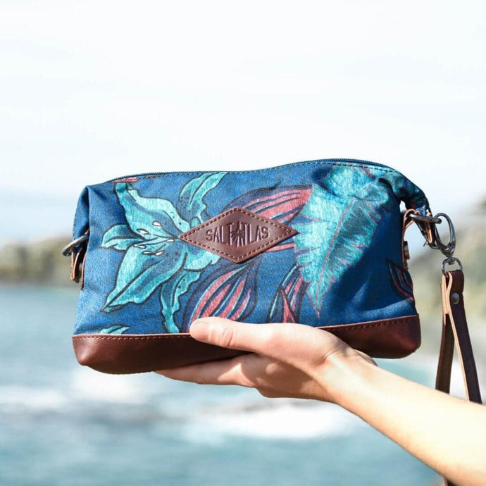 hand of a woman holding the salt atlas rover crossbody bag in blue lily print with a ocean view background