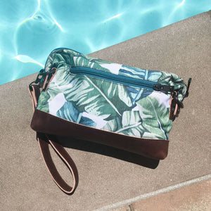 back of the salt atlas rover crossbody bag in island green print next to a swimming pool