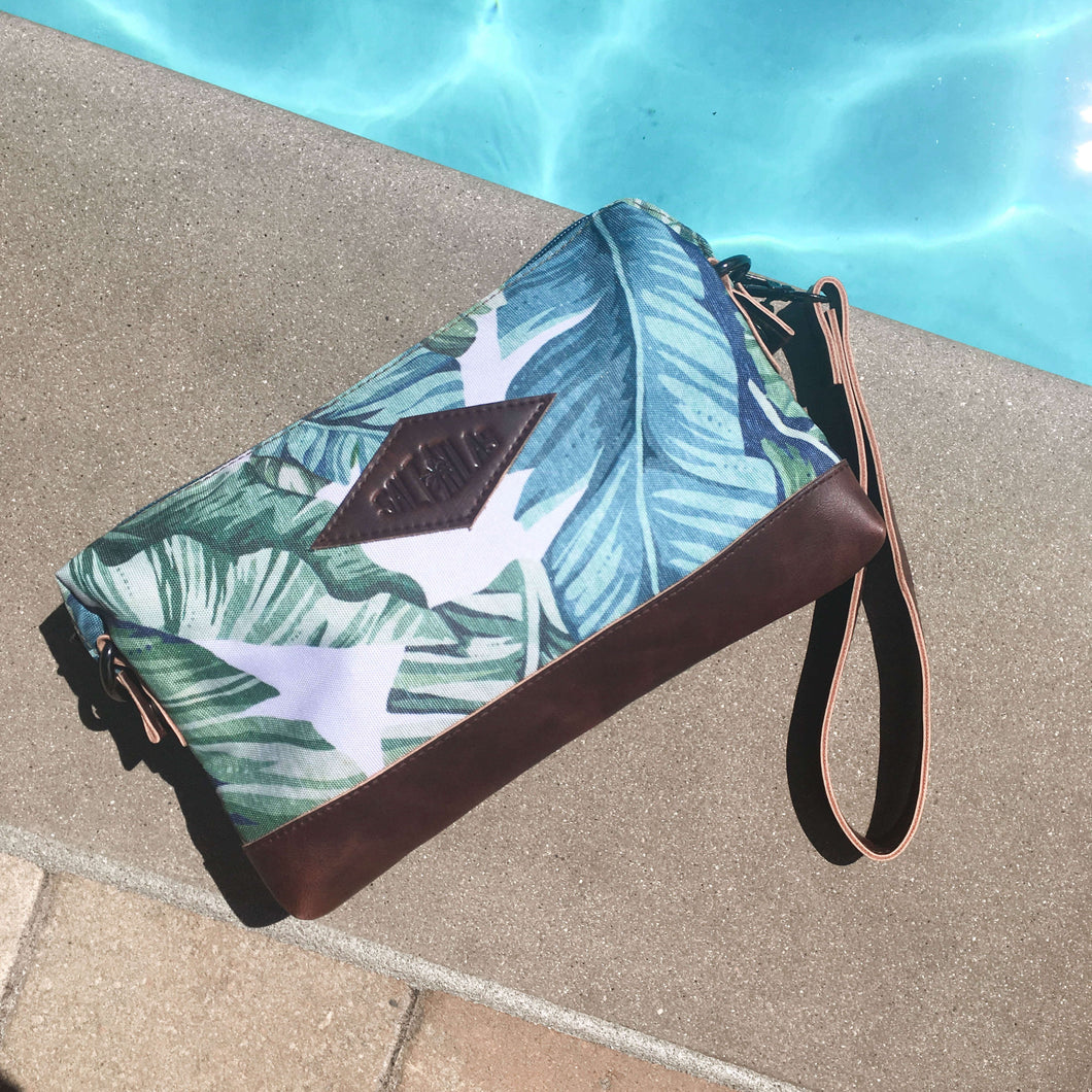 front of the salt atlas rover crossbody bag in island green print next to a swimming pool