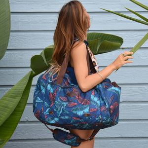 woman the salt atlas voyager duffle in blue lily print in front of a blue wooden-made wall and vegetation