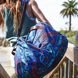 Woman carrying the salt atlas voyager duffle in blue lily print on her way to the beach