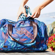 Load image into Gallery viewer, Woman putting a water bottle inside the salt atlas voyager duffle in blue lily print