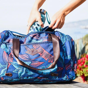 Woman putting a water bottle inside the salt atlas voyager duffle in blue lily print