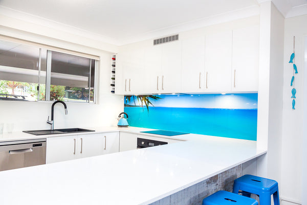 newly renovated kitchen with white benches a black sink and a spectacular photo splashback on North Stradbroke Island