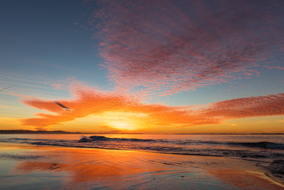 amazing sunset at the beach with red and orange colours and cloud formation resembling an eye