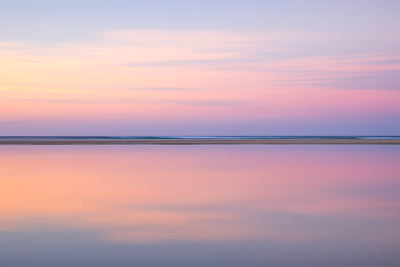 very calm still waters and pink pastel sunset colours reflected in the still lagoon
