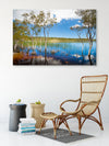 wall art canvas of peaceful Brown Lake framed by paperbark trees on the wall with a cane chair in front