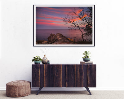 sunset over the ocean with wispy red clouds framed wall art print on the wall above a retro buffet cupboard