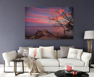 sunset with beautiful wispy clouds rocks trees and the ocean wall art canvas on a living room wall