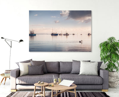 a pelican swims along on calm waters with boats in the background peaceful wall art canvas in a living room with neutral sofa