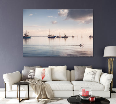 a living room with dark purple wall features an art photograph canvas of a peaceful morning with a pelican swimming in front of boats
