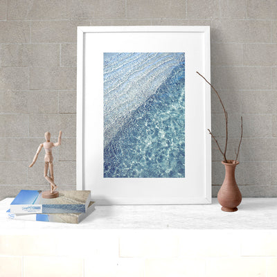 modern wall art print of blue water ocean ripples in a white frame leaning against the wall on a white desk