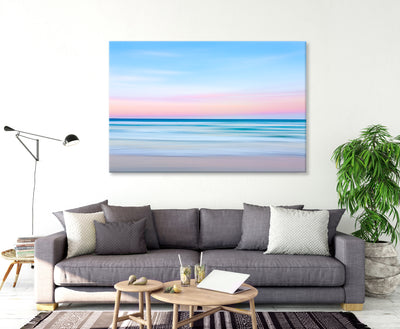 blue pink pastel coloured artistic wall art image of the ocean at sunset canvas print on the wall in a living room
