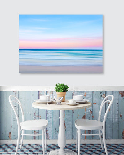 blue pink pastel coloured artistic wall art image of the ocean at sunset on the wall at a cafe