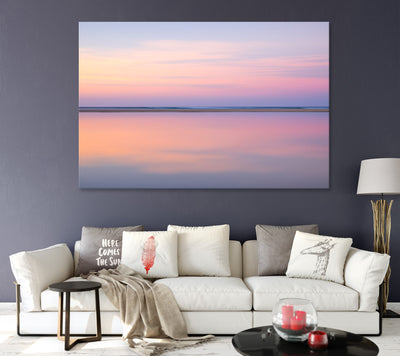 living room with dark purple walls featuring a framed wall art print of pastel pink abstract image of still calm waters at sunset on North Stradbroke Island also called Straddie