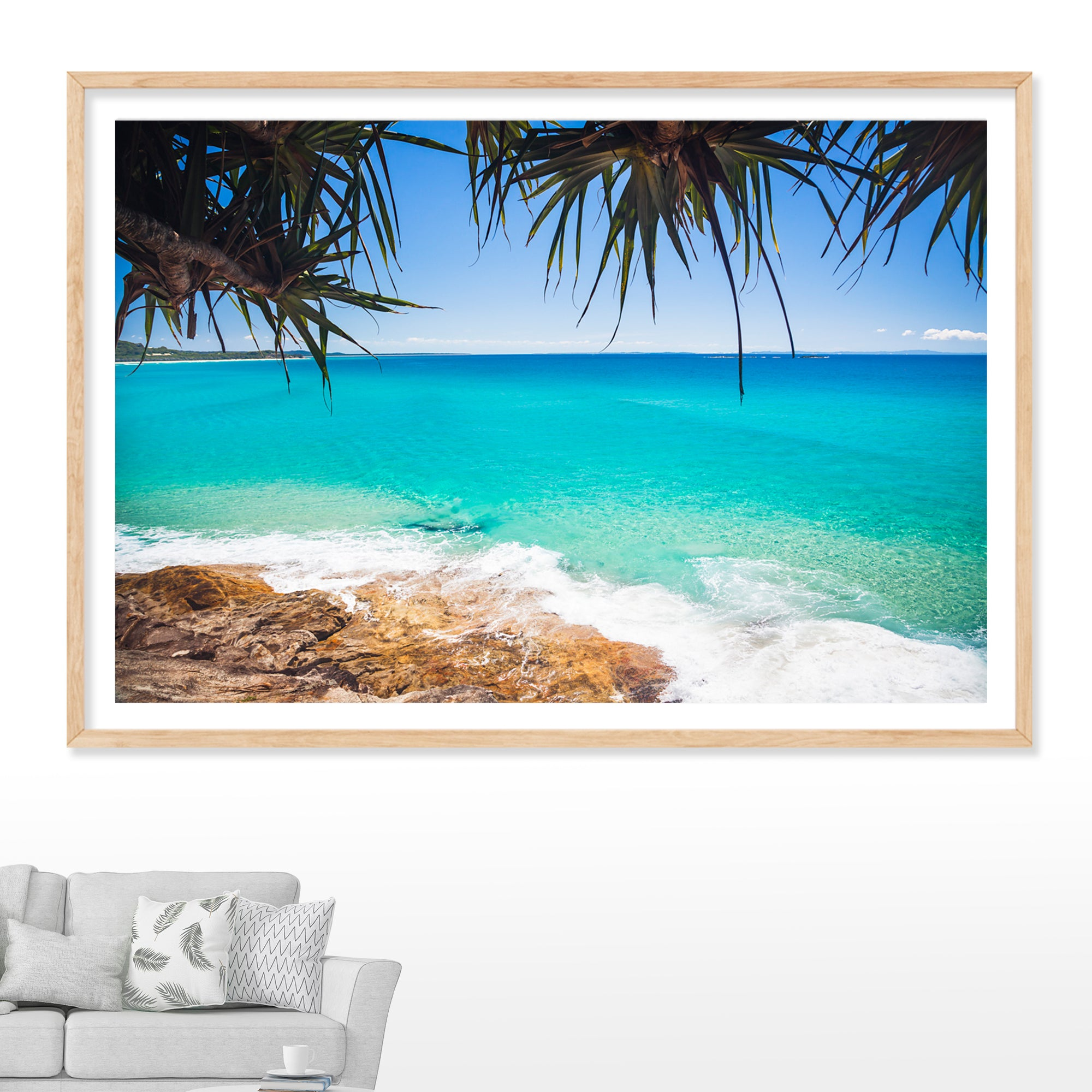 wall art photograph of north stradbroke island with calm blue ocean a pandanus palm hanging overhead and rocks below