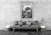 a living room featuring a wall art print of a pandanus palm and a boardwalk in black and white