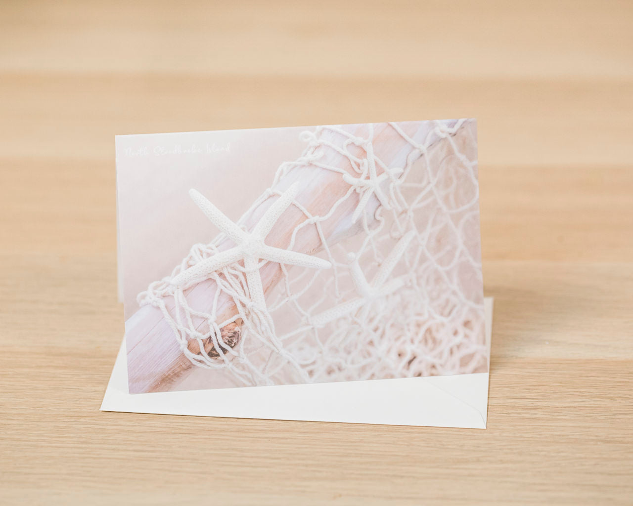 Greeting card and envelope. Neutral coloured starfish and net on driftwood taken at Amity Beach, North stradbroke Island by Julie Sisco