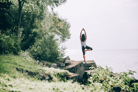 Woman near edge of woods standing on a rock overlooking water in yoga pose