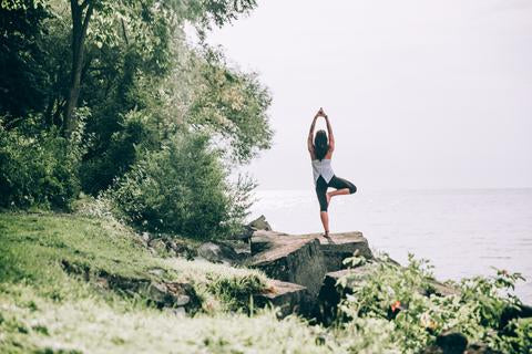 Woman on rock overlooking water in yoga pose