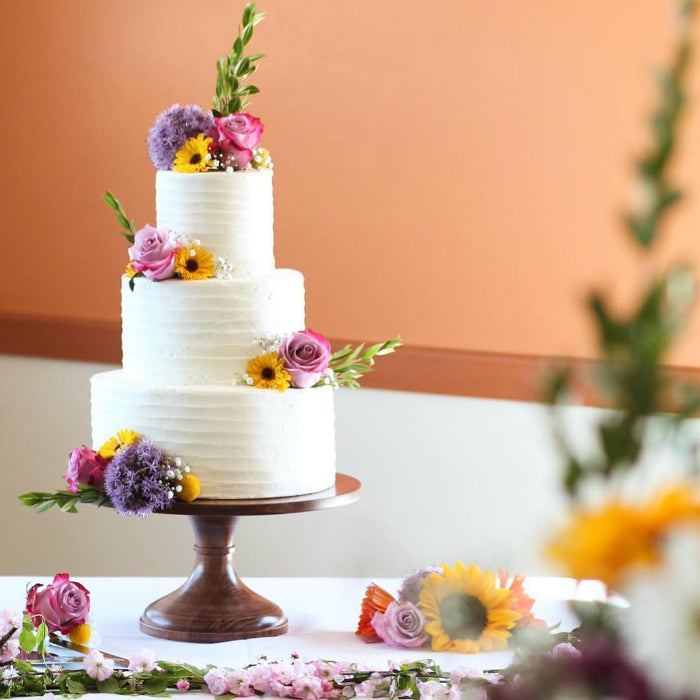 White Cake with Flower Accents on 14 inch Natural Wood Cake Stand