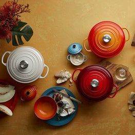 Arrangement of Le Creuset casserole dishes in various colours and sizes
