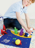 boy playing with Oskar & Ellen rocket ship and aliens on planet mat