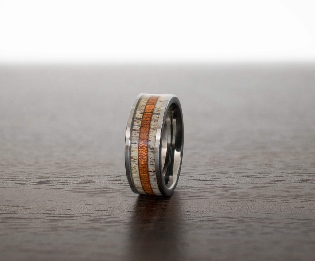 antler-wood-mens-wedding-band-in-abalone-shell-on-table-with-slight-view