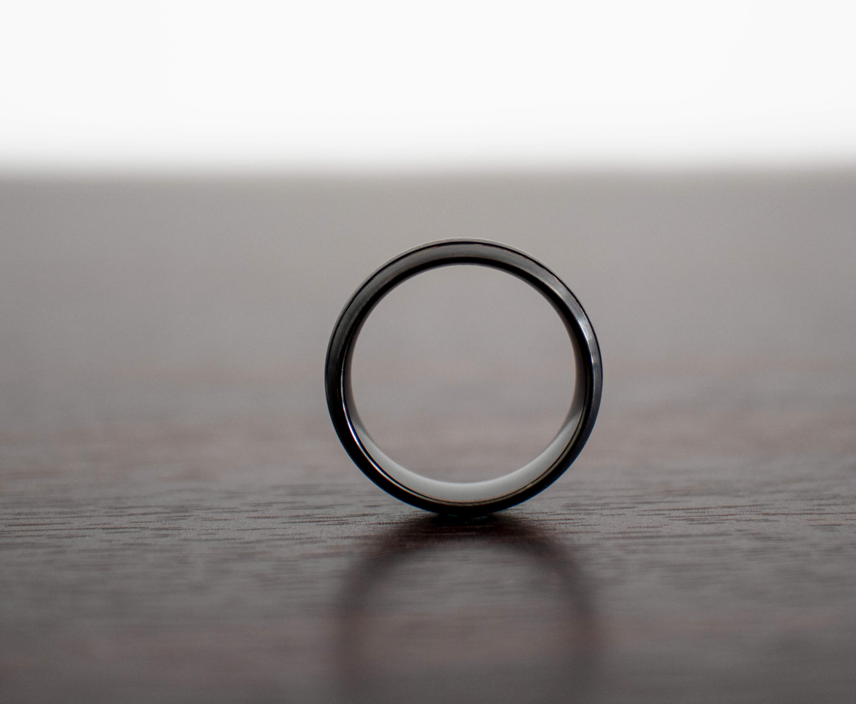 black-mens-wedding-band-on-table-side-view