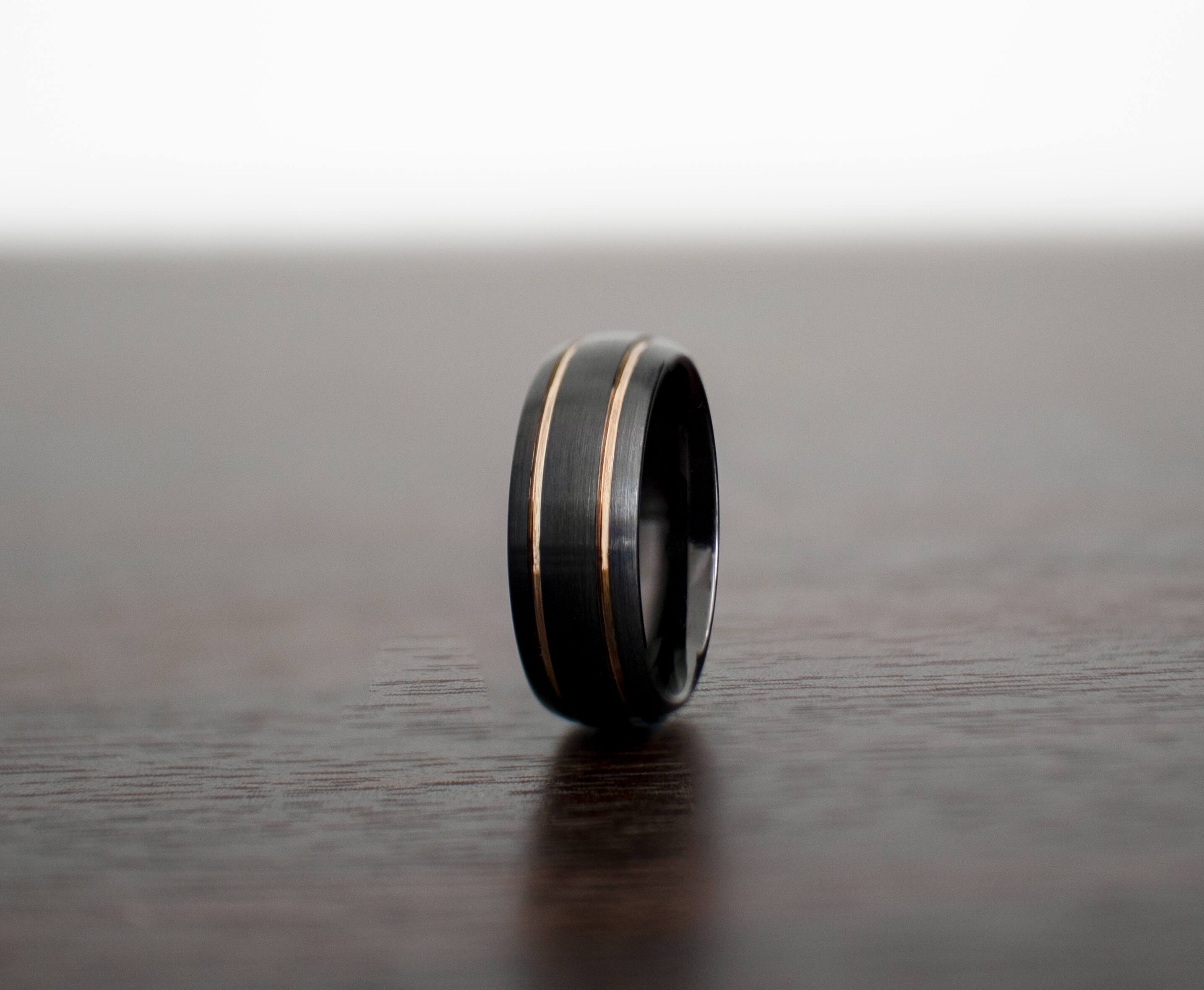 black-mens-wedding-band-on-table-slight-view